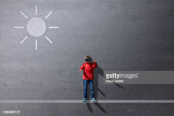 Boy wearing VR goggles standing under imaginary painted sun