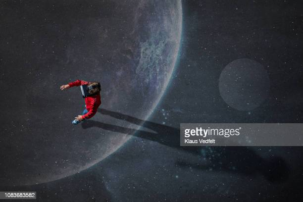 Boy wearing VR goggles walking across imaginary painted planet in space