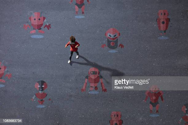 Boy wearing VR goggles walking among painted imaginary robots