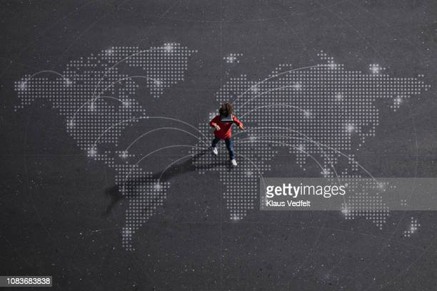 Boy wearing VR goggles walking on painted imaginary world map