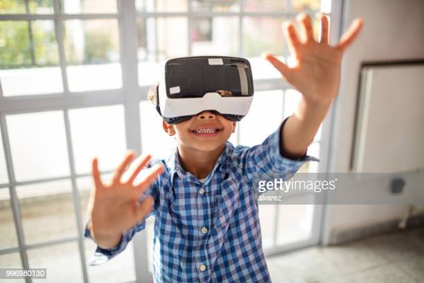 Boy wearing VR headset while gesturing in class