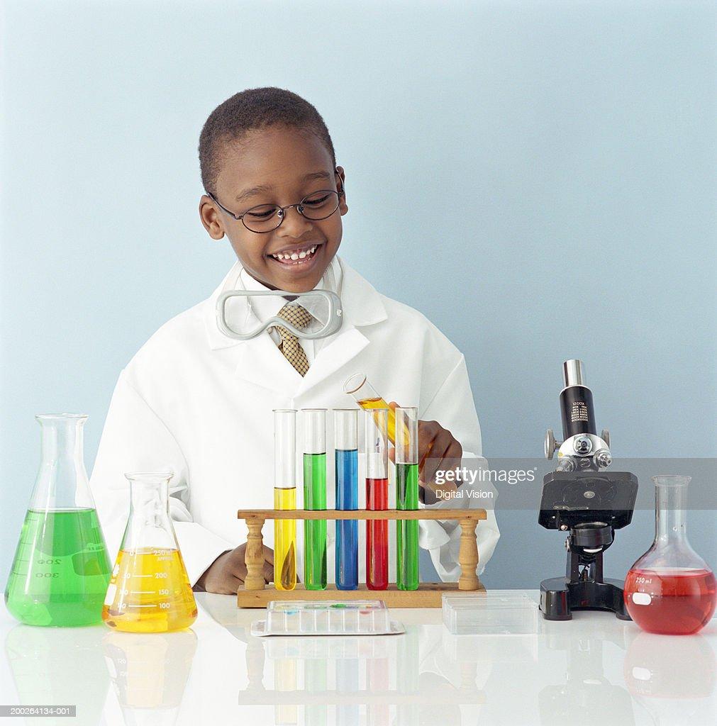 Boy (5-7) wearing white coat holding test tube in laboratory, smiling : Stock Photo