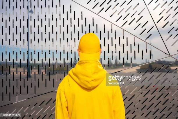 boy wearing yellow sweatshirt in front of metallic wall on sunny day - hooded top stock pictures, royalty-free photos & images
