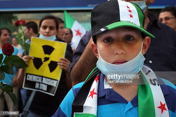 A boy wears a cap baring the flag of the Syrian opposition and rebels as Syrian immigrants living in Bulgaria protest against the recent massacre of...