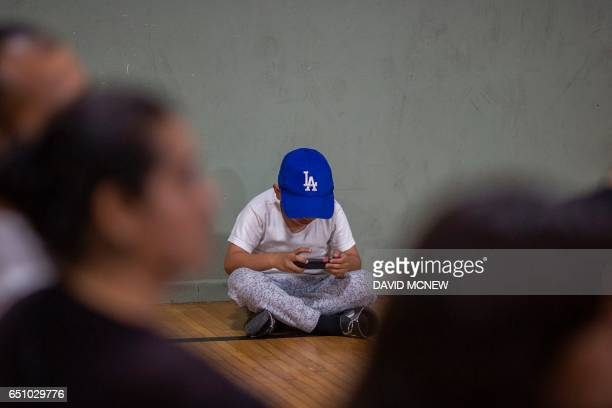 A boy wears a Los Angeles logo cap and plays an electronic game at a workshop for immigrants to make a preparedness plan in case they are confronted...