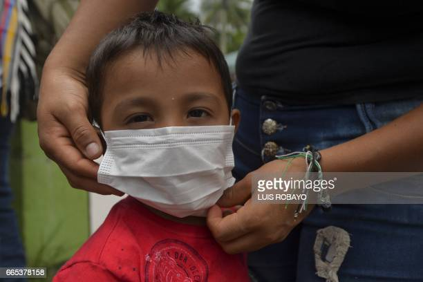 A boy wears a mask during an emergency vaccination programme following mudslides in Mocoa Putumayo department Colombia on April 6 2017 The landslide...