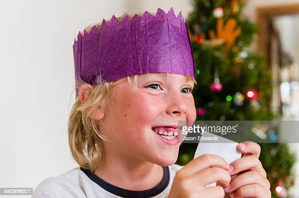 A boy wears a paper hat and reads a joke from a bon bon on Christmas Day.