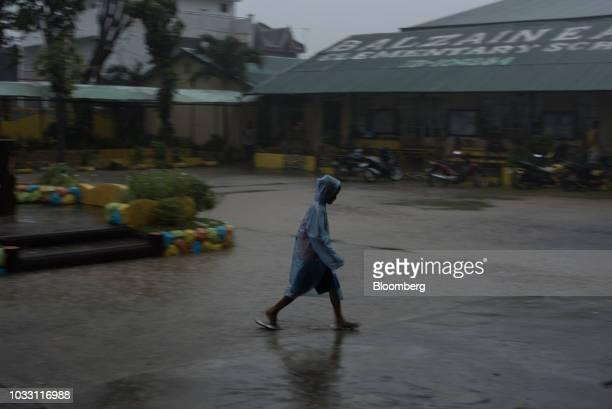 A boy wears a rain coat in heavy rainfall outside the temporary evacuation center at Balzain East Elementary School ahead of Typhoon Mangkhut's...