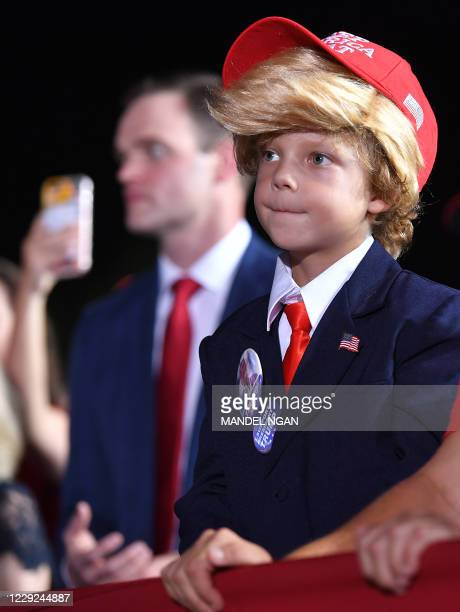 Boy wears a Trump wig as US President Donald Trump speaks during a campaign rally at Pensacola International Airport in Pensacola, Florida on October...