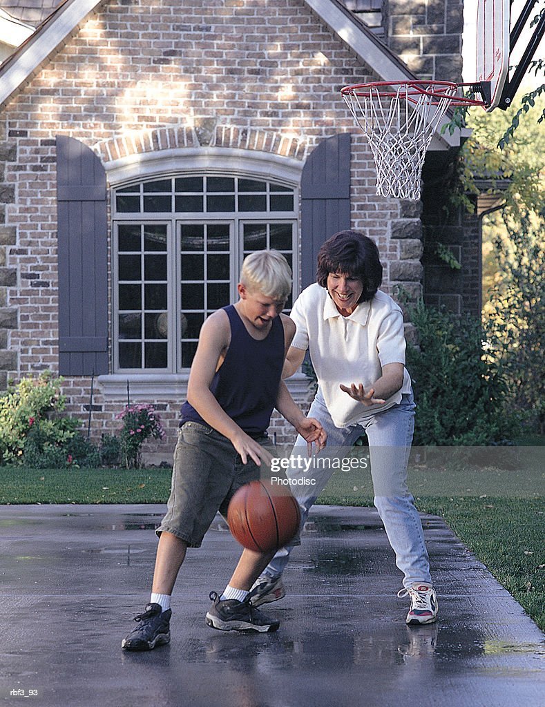 boy wears green shorts black top plays basketball cement court with mother wears white shirt jeans : Stockfoto