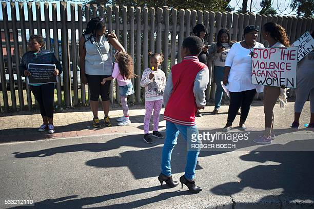 A boy wears high heel shoes during a protest against ongoing violence against women in Gugulethu on May 21 about 20 Km from the centre of Cape Town...