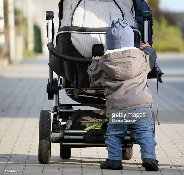 Boy wheeling his own buggy