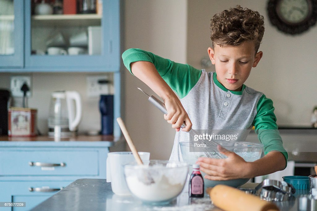 Boy whisking batter in bowl at kitchen counter : Stock Photo