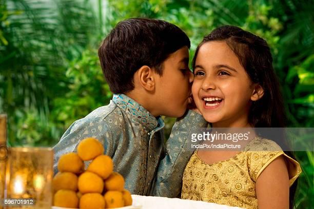 Boy whispering in his sisters ear