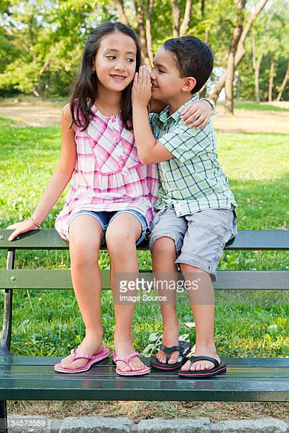Boy whispering secrets to girl on park bench