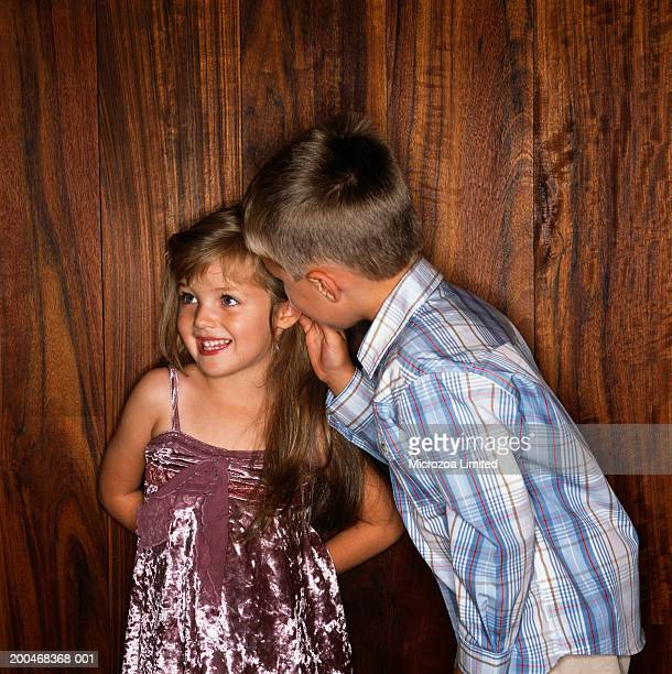 boy (3-5) whispering to girl (2-4), smiling - microzoa stockfoto's en -beelden