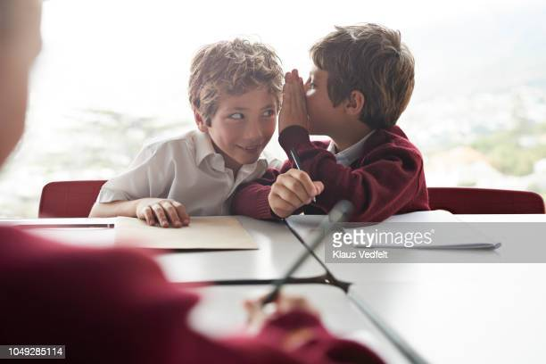 boy whispers in friends ear in classroom at school - rumor stock pictures, royalty-free photos & images