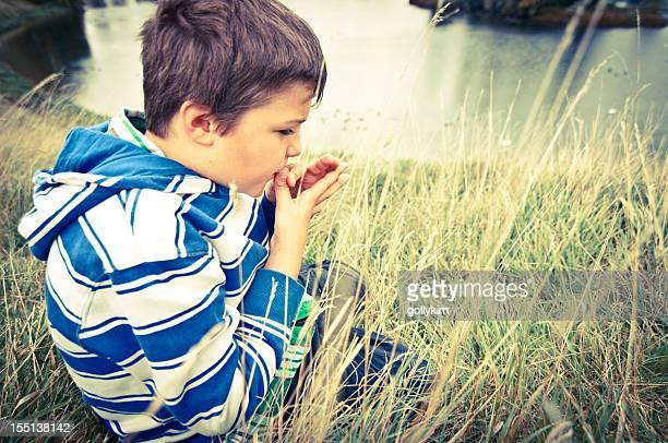 Garçon faire avec un brin d'herbe