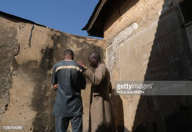 Boy who escaped from gunmen stand with his father in their home after gunmen abducted students at the Government Science Secondary school on in...