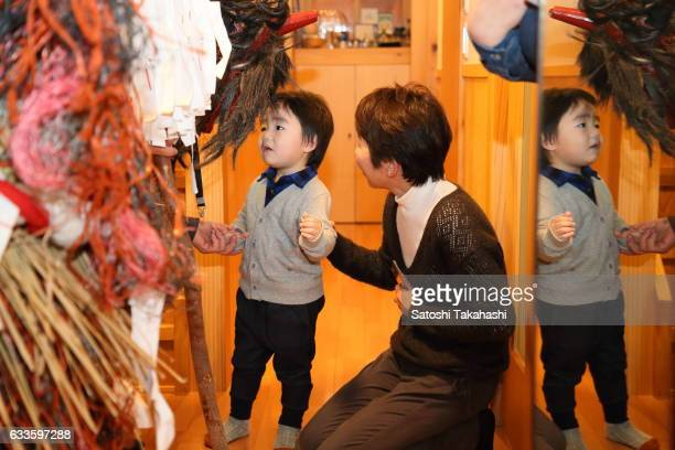 A boy who is frightened by the visit of Namahage deities during the Namahage festival of traditional folk event on New Year's Eve Namahage deities...