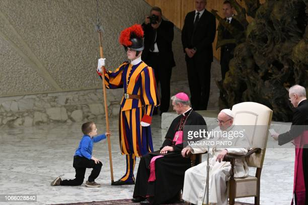 A boy who jumped from the audience onto the stage plays with a Swiss Guard's spear as Pope Francis and Prefect of the Papal Household Georg Ganswein...