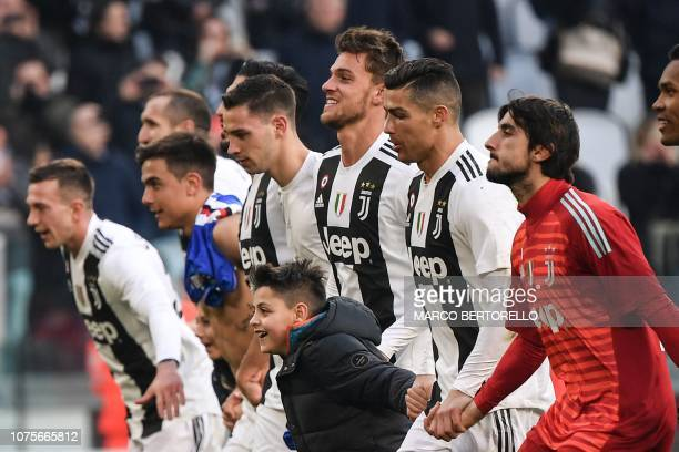 A boy who took to the pitch after the game celebrates with Juventus' Portuguese forward Cristiano Ronaldo and teammates after Ronaldo invited him to...