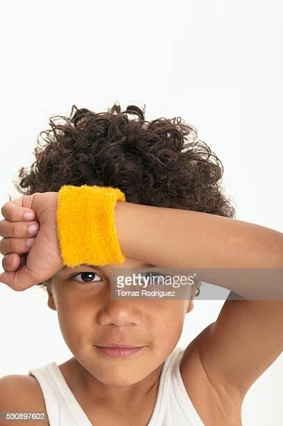 boy wiping his forehead with yellow wristband - cinta deportiva del pelo fotografías e imágenes de stock