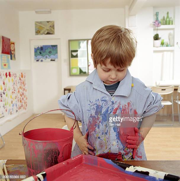 Boy (4-6) wiping paint covered hands down shirt