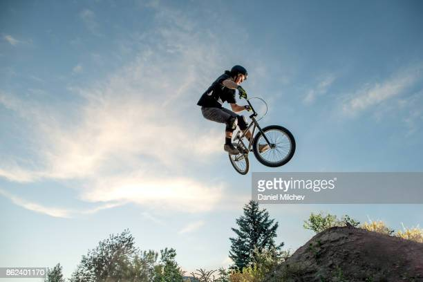 Boy with a bmx jumping againds blue sky during sunset.