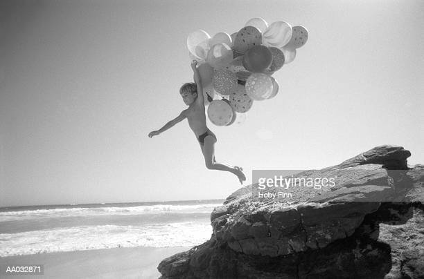 boy with a bunch of balloons jumping off of a rock - speedo boy stock photos and pictures