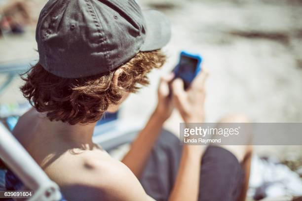 A boy with a cap sitting on the beach and looking at his phone