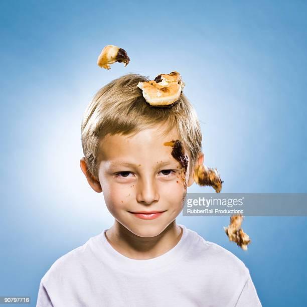 boy with a chocolate doughnut falling on his head