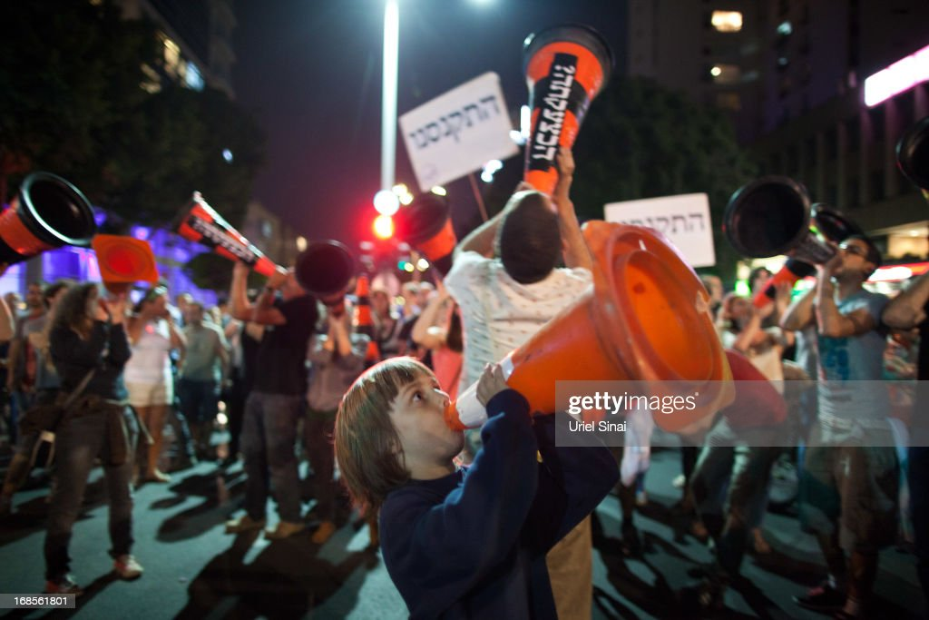 A boy with a cone marches with demonstrators through the streets to protest against Israeli Finance Minister Yair Lapid's budget cuts on May 11, 2013 in Tel Aviv, Israel. Thousands of Israelis took to the streets to protest against austerity measures presented this week as part of the state's new budget.