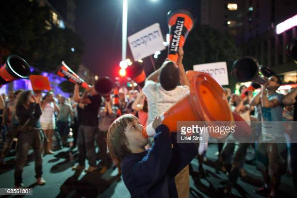 A boy with a cone marches with demonstrators through the streets to protest against Israeli Finance Minister Yair Lapid's budget cuts on May 11 2013...