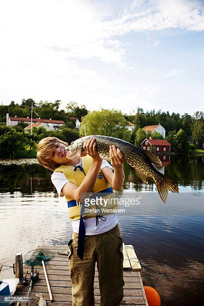 a boy with a fish on a jetty sweden. - pike fish stock pictures, royalty-free photos & images