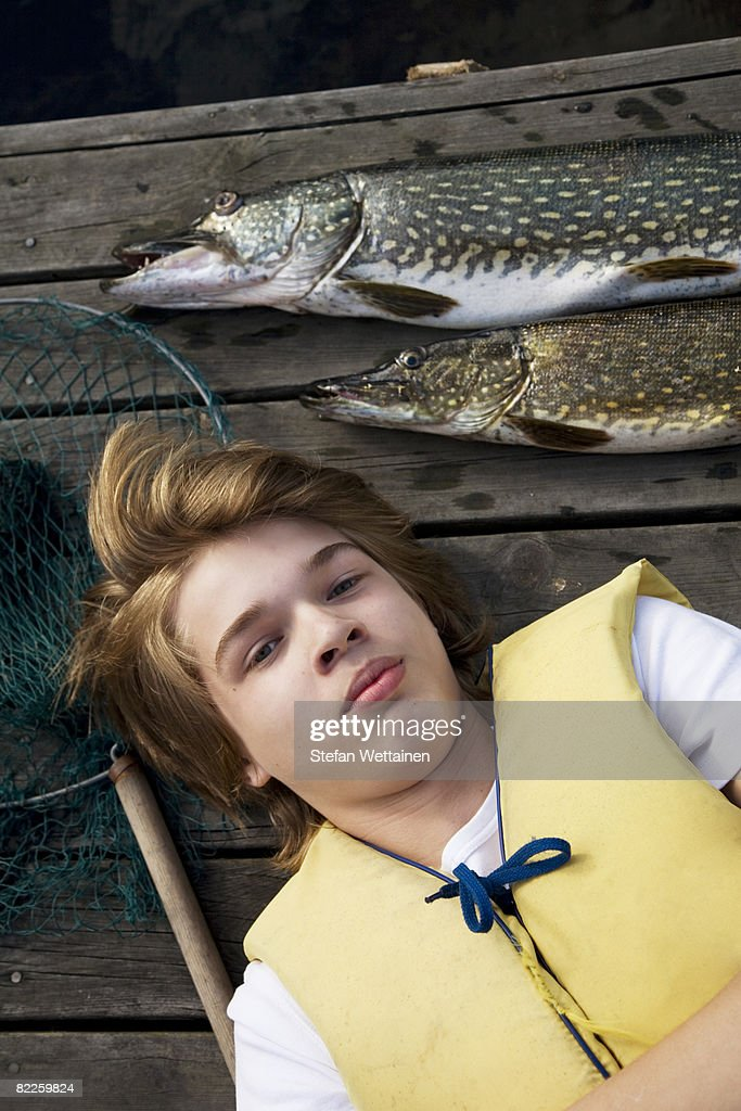 A boy with a fish on a jetty Sweden. : Stock Photo