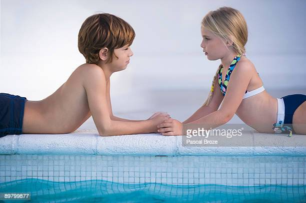 Boy with a girl lying at the poolside
