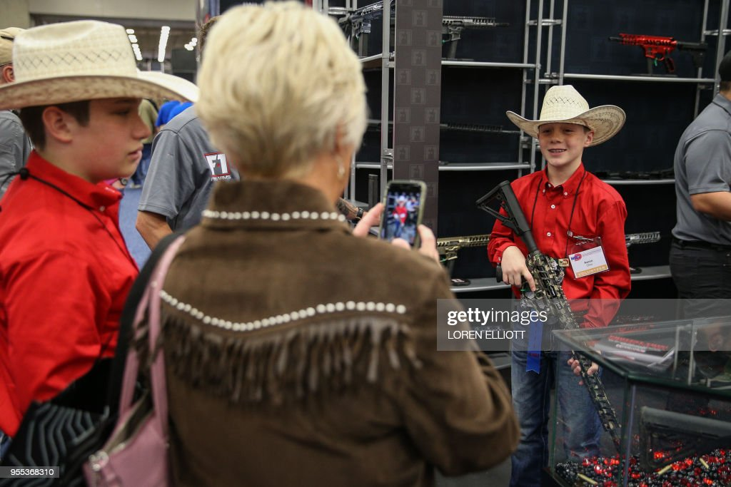 A boy with a gun poses for a photo in an exhibit hall at the Kay Bailey Hutchison Convention Center during the NRA's annual convention on May 6, 2018 in Dallas, Texas.