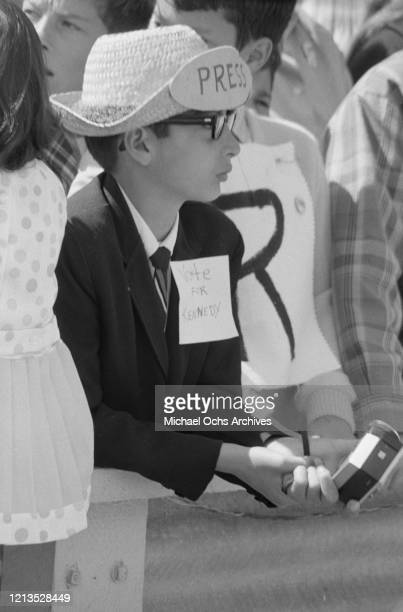 A boy with a homemade press badge and 'Vote for Kennedy' sign at Monterey Peninsula Airport in California during a visit by American politician and...