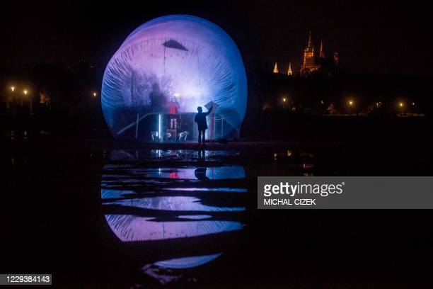 Boy with a kite looks on a girl with a kite and standing in a plastic bubble during a performance by an artistic group Cirk La Putyka called...