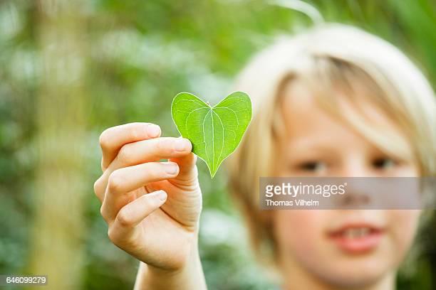 Boy with a leaf shaped like a heart