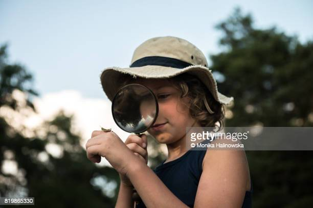 Boy with a magnifying glass in a forest