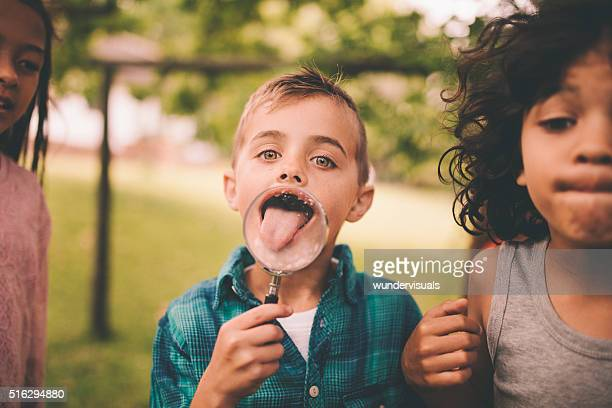 Boy with a magnifying glass making his tongue look big