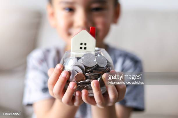 a boy with a piggy bank and a house model,saving money for home,home insurance concept, - prosperity stock pictures, royalty-free photos & images