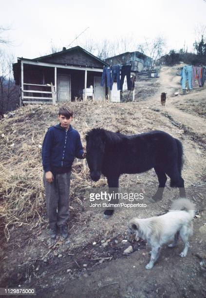 A boy with a pony and a dog in a village Pike County Kentucky US 1967