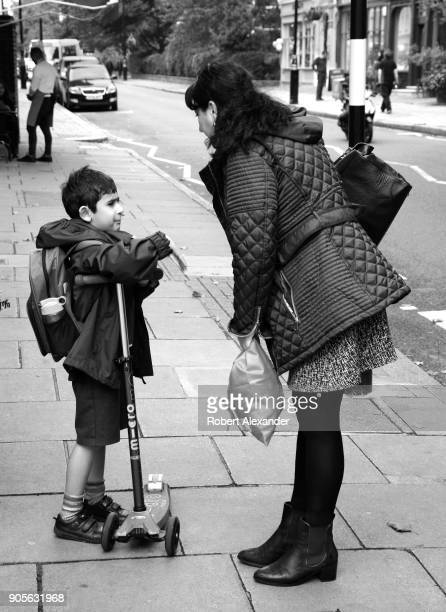A boy with a push scooter and backpack gets a gentle scolding from his mother on a sidewalk in the Belgravia district of London England
