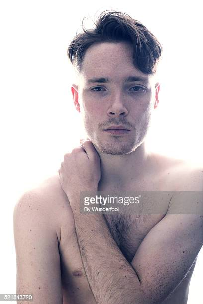 boy with a scruffy freckled face looking sad in the camera - hairy chest stock-fotos und bilder