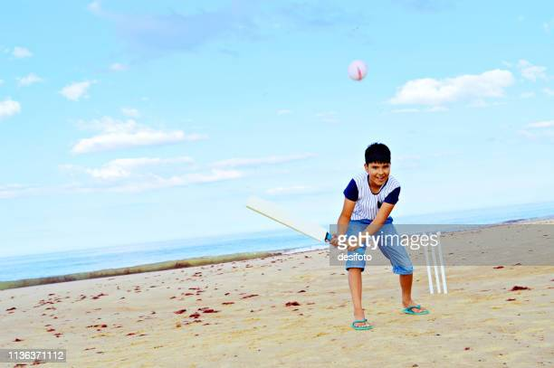 a boy with a smile batting on a sea beach in a summer day, clouds in blue sky, aqua blue sea in backdrop, flips the white color ball with foot forward and bat in air. - beach cricket stock pictures, royalty-free photos & images