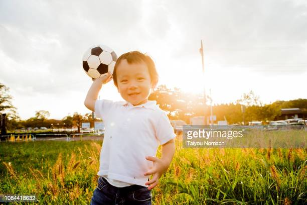 a boy with a soccer ball in hand - asian boy stock pictures, royalty-free photos & images