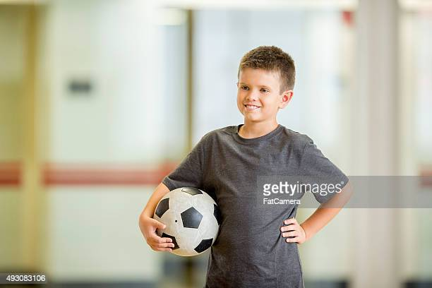 boy with a soccer ball - tee sports equipment stock photos and pictures